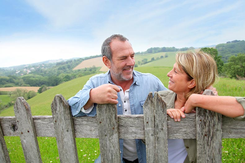 A smiling active adult couple leaning on fence in the countryside