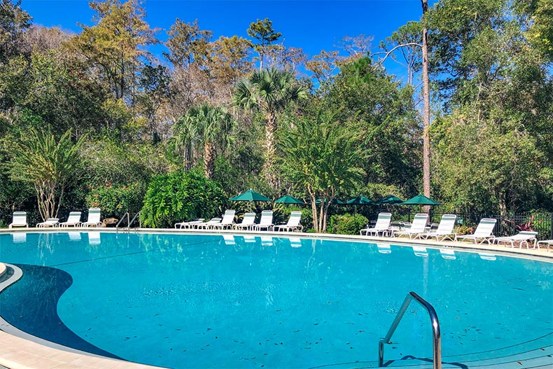 Lounge chairs on the patio surrounding the outdoor pool at Huntington at Hunter's Ridge in Ormond Beach, Florida