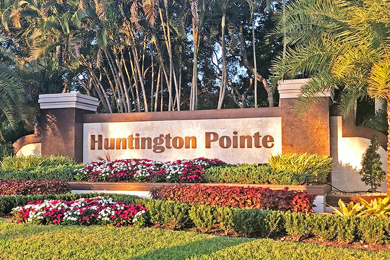 Trees, flowers, and bushes surrounding the community sign for Huntington Pointe in Delray Beach, Florida