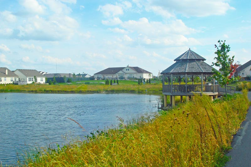 scenic lake and gazebo at sun city huntley with homes in background