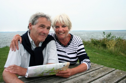 An older adult couple sitting together at a picnic table on the coast while looking at a map