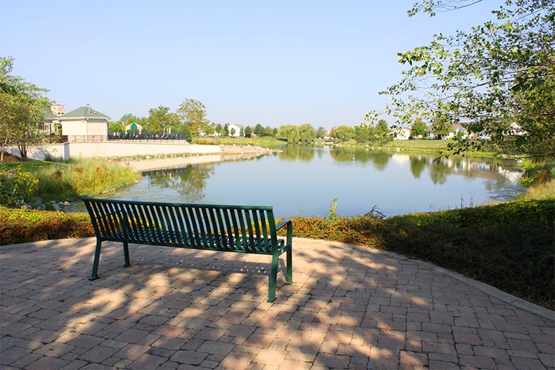 View of a bench facing a pond surrounded by landscaped greenery at Grand Haven in Romeoville, Illinois