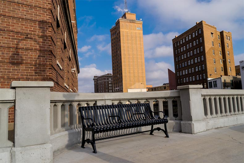 A bench on a walkway with buildings in the background in Aurora, Illinois