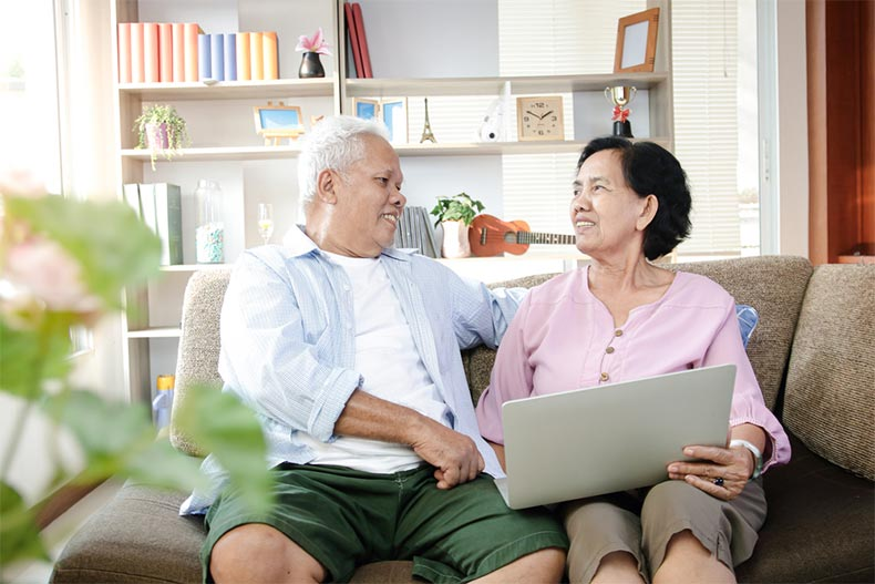 A senior couple sitting on a sofa while looking over their Social Security benefits online