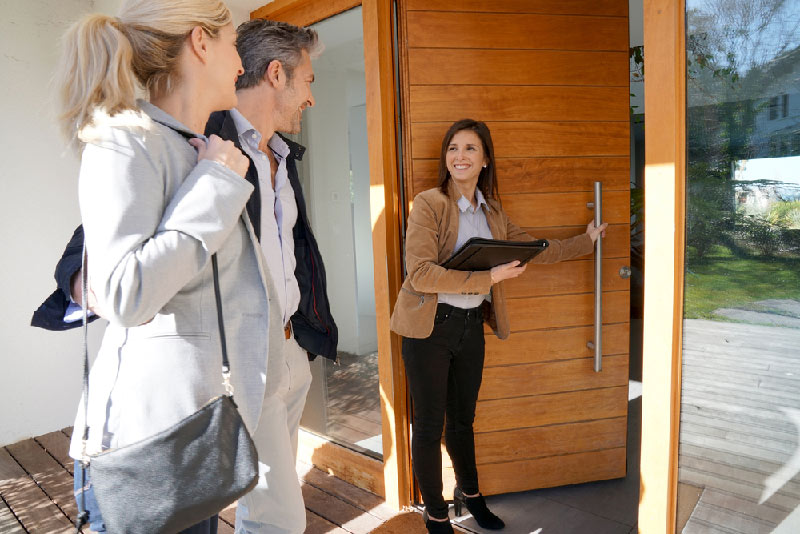 real estate agent holding home door open for couple looking to buy.