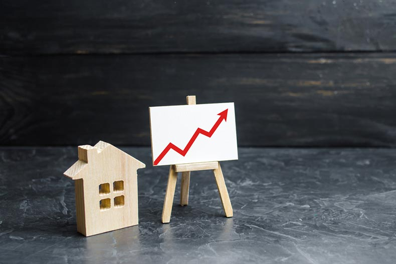 A wooden house silhouette beside a chart with a red arrow pointing upwards