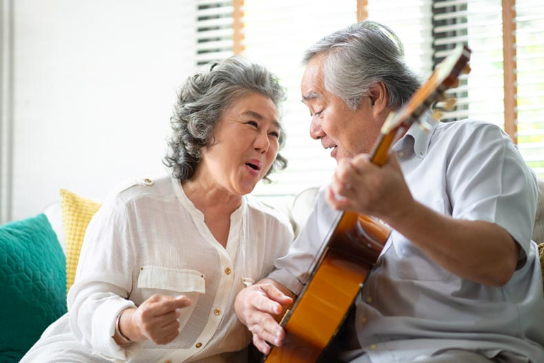 A senior couple sitting on a couch while singing and playing acoustic guitar together