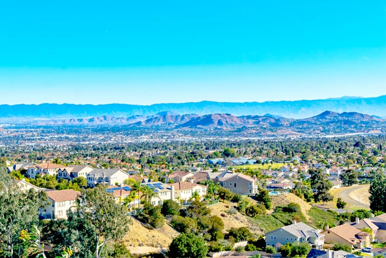 View of houses and trees with mountains in the distance in Inland Empire in Southern California