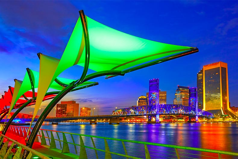 Lighted fixtures on the shores of St. Johns River with Jacksonville skyline