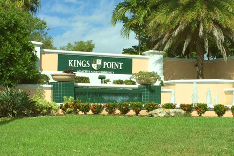 Greenery and a water feature surrounding the community sign for Kings Point in Tamarac, Florida