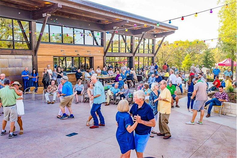 Group of seniors dancing and socializing in outdoor space at Kissing Tree clubhouse
