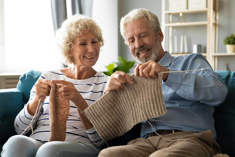 Older couple knitting on the couch
