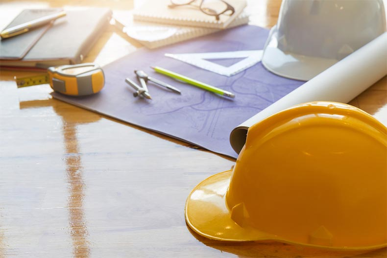 Blueprints, hard hats, and tools on a wooden table