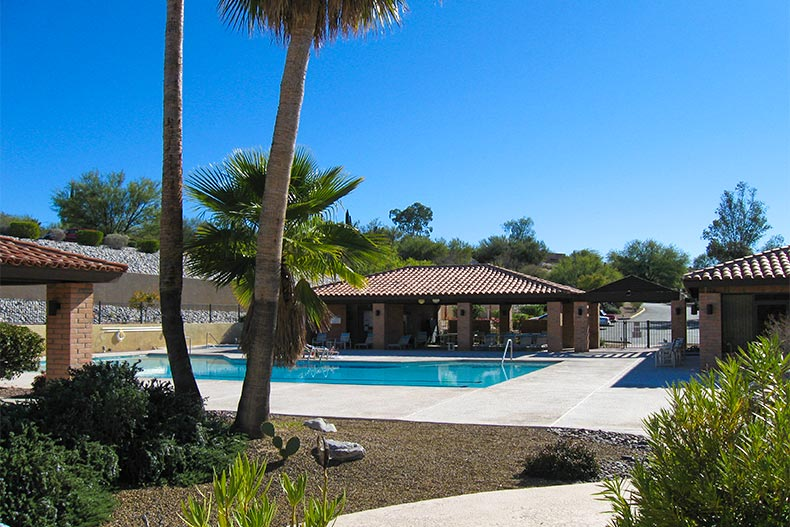 Outdoor pool and patio with clubhouse buildings in La Cholla Hills