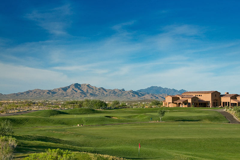 arizona golf course with clubhouse in the distance and mountains in the background