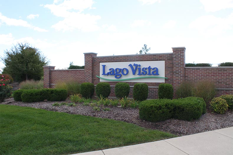 Greenery surrounding the community sign for Lago Vista in Lockport, Illinois