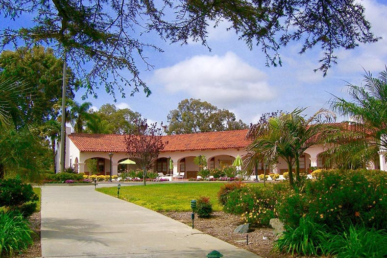 Lush greenery and a Spanish Revival style building at Laguna Woods Village in Laguna Woods, California