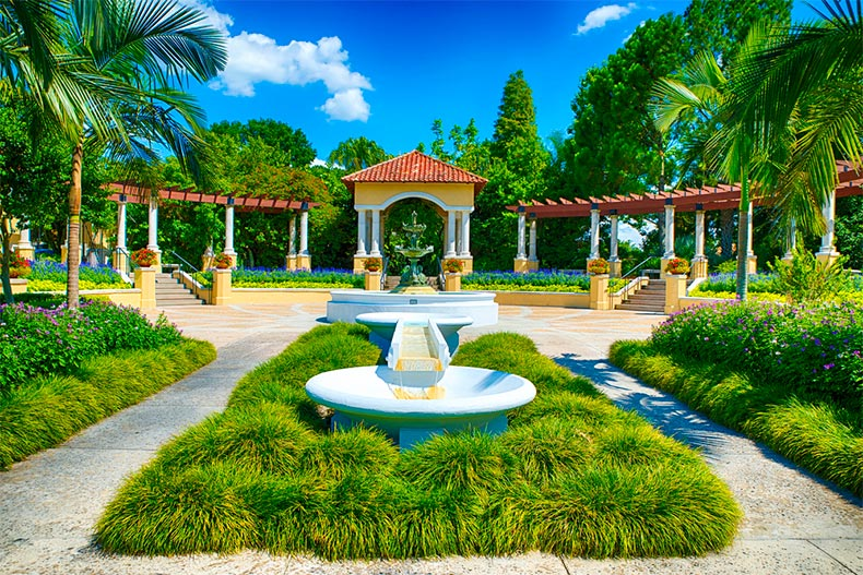 Palm trees and well-manicured greenery surrounding a courtyard with a fountain in Lakeland, Florida