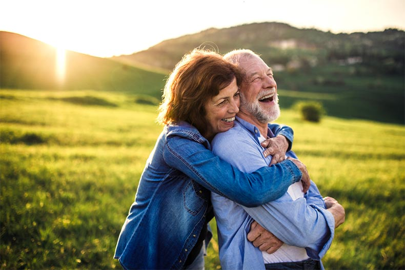 An older couple hugging and laughing in an open field