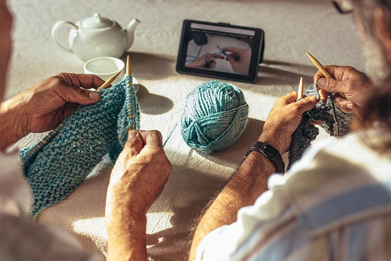 Hands of senior men holding knitting needles and wool yard while sitting at table and learning knitting from online videos