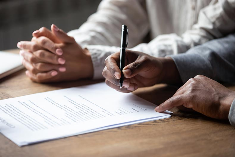 Close up on hands signing a loan agreement with a mortgage lender