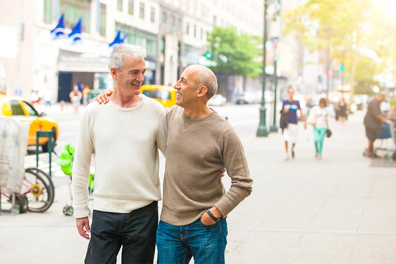 Older LGBTQ couple arm in arm walking around New York City