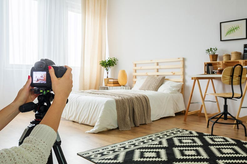 A real estate agent taking a photo of a staged bedroom for a listing