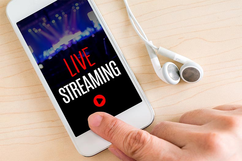 Closeup on a hand pressing the play button on a smart phone livestreaming a concert
