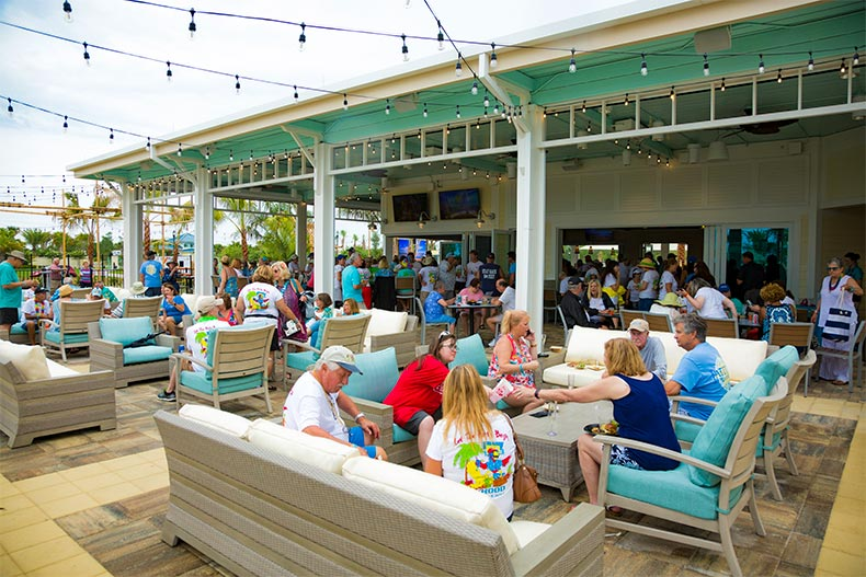 Residents and visitors enjoying the outdoor patio at a bar in Latitude Margaritaville