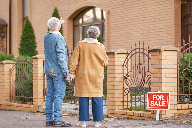 Senior couple with their backs to the camera looking at a home for sale