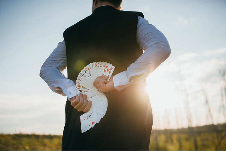 Man holding cards behind his back for magic trick