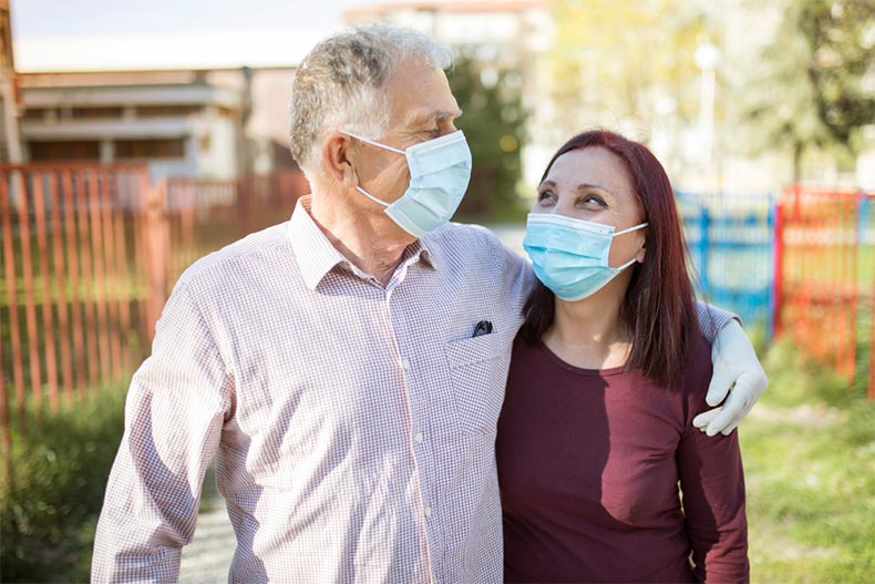 An active adult couple wearing medical masks and gloves while touring a home for sale