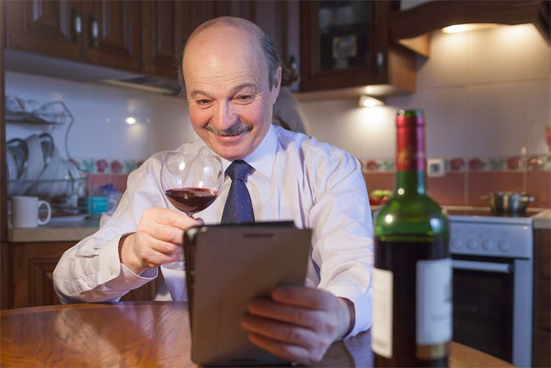 An elderly man in a shirt and tie toasting with a glass of wine via video chat