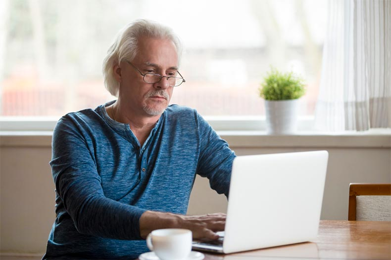 Older man sitting at desk with coffee and typing on a laptop