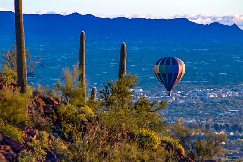 Hot air baloon peaking past a mountain peak with city of Marana and mountain range in the background