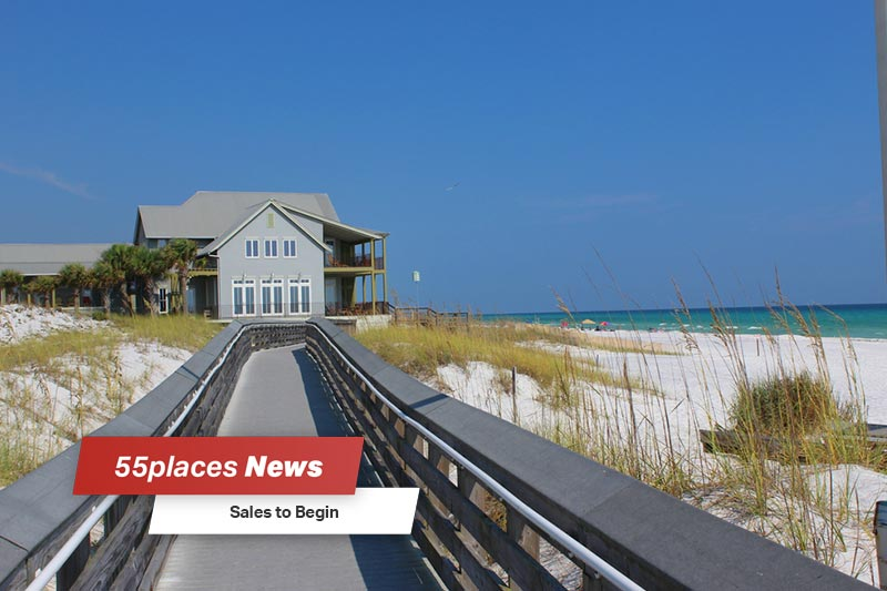 """Sales to Begin"" banner over a view down a boardwalk along the beach in Watersound, Florida"