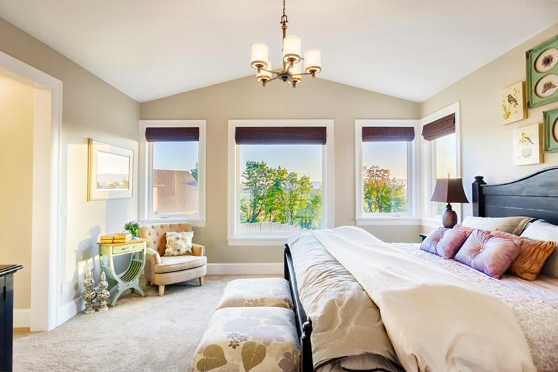 modern master bedroom with bed and chair and sun coming through window