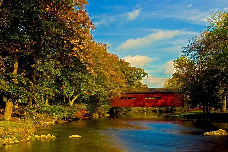 Fall colors surrounding a covered bridge going over river in Mechanicsburg