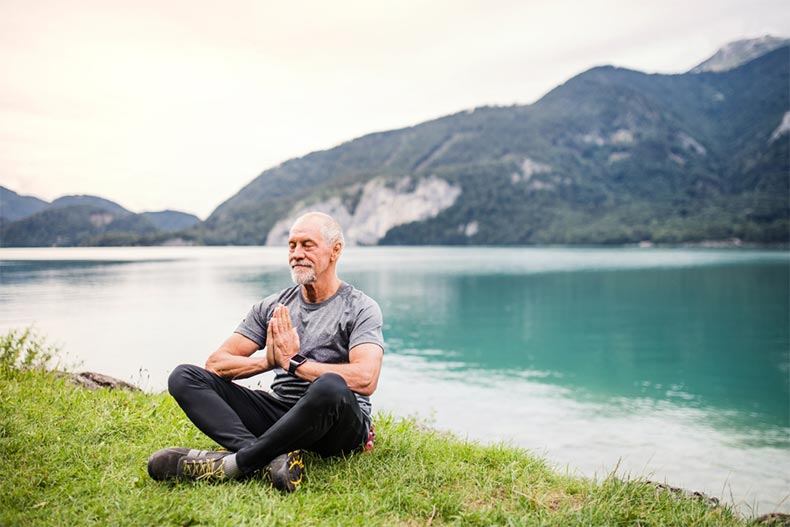 A senior man sitting beside a picturesque lake and meditating