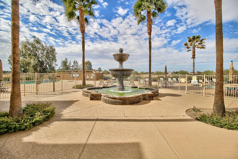 A fountain surrounded by palm trees at Mission Royale in Casa Grande, Arizona