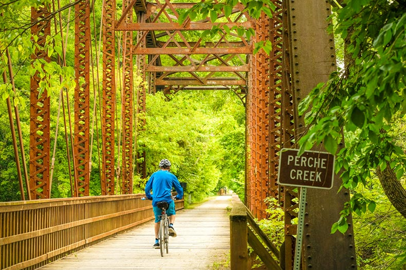 A bicyclist riding over an old railroad bridge in Missouri State Park in the late afternoon