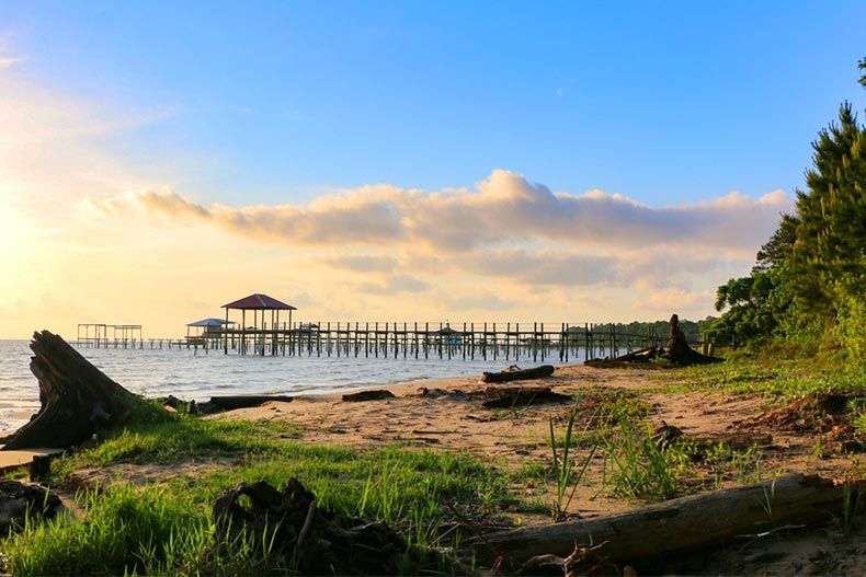 The shoreline along Mobile Bay in Alabama during late afternoon with a pier in the background