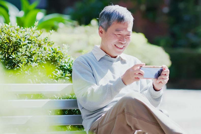 An senior man sitting on a park bench and smiling while playing a game on his phone
