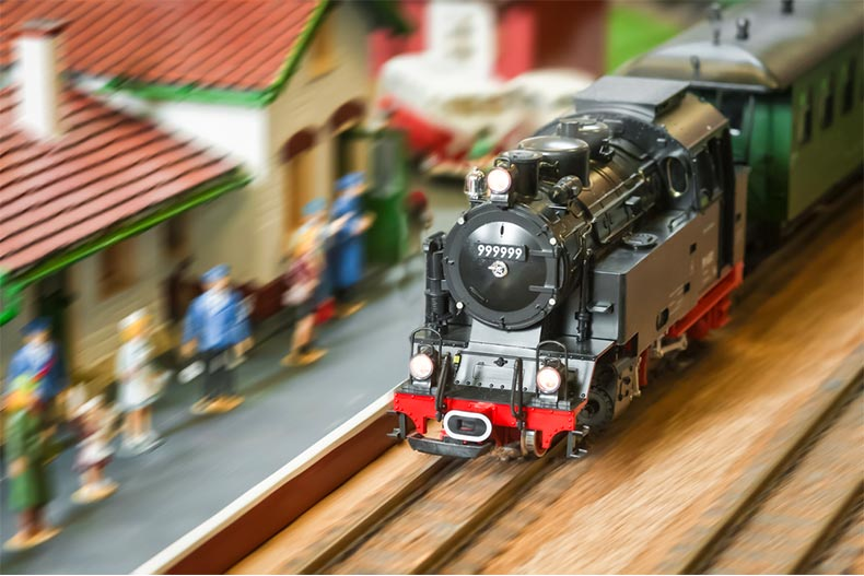 Closeup of model train pulling into a station
