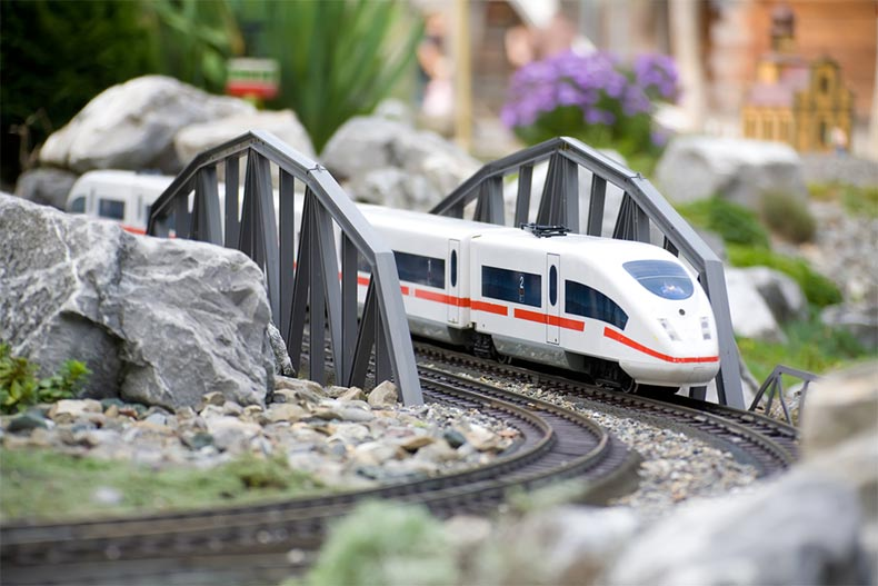 Bullet model train set riding on rails through scenery