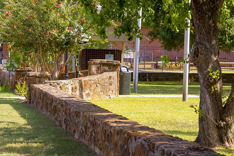 A stone wall along a public park in Montgomery, Texas