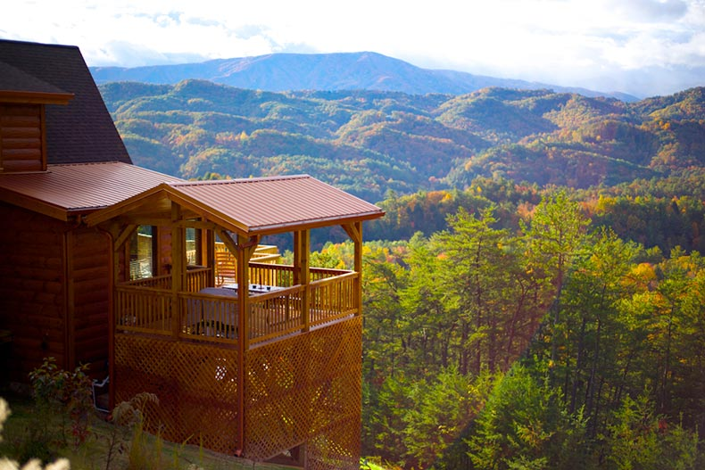 A luxury cabin with a deck overlooking a picturesque view of the Blue Ridge Mountains in North Carolina