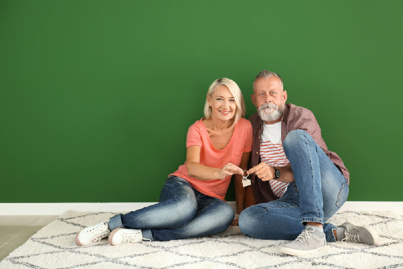 older couple against green wall smiling
