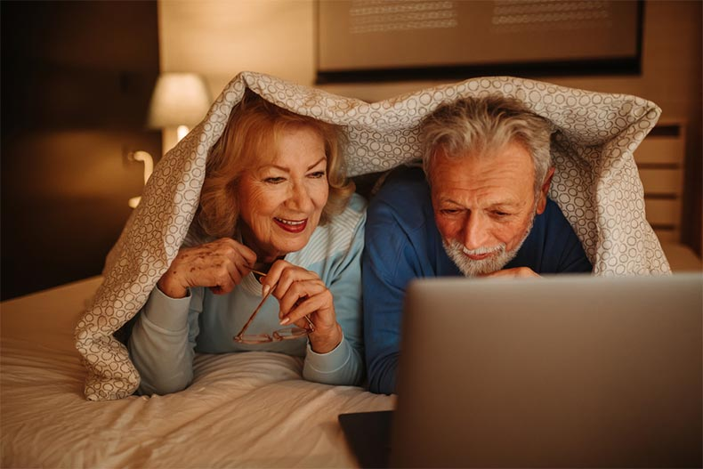An older couple on a bed under covers watching a movie