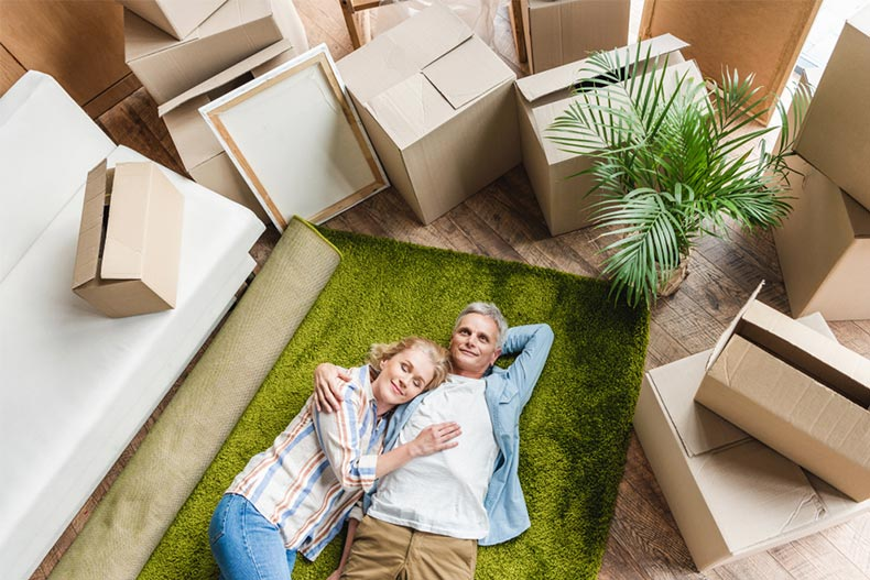 High angle view of a happy senior couple lying on a green carpet surrounded by moving boxes